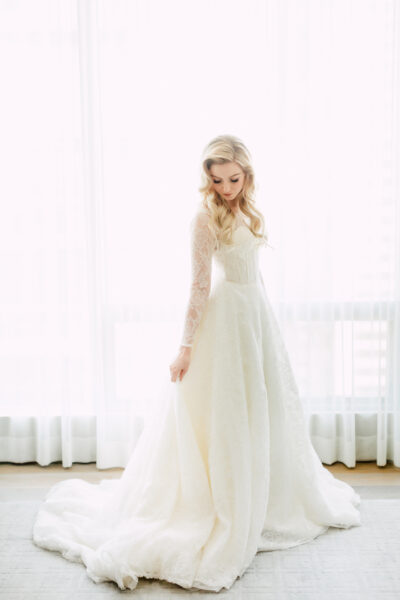 Blonde bride in modest long sleeve wedding dress at Four Seasons Toronto