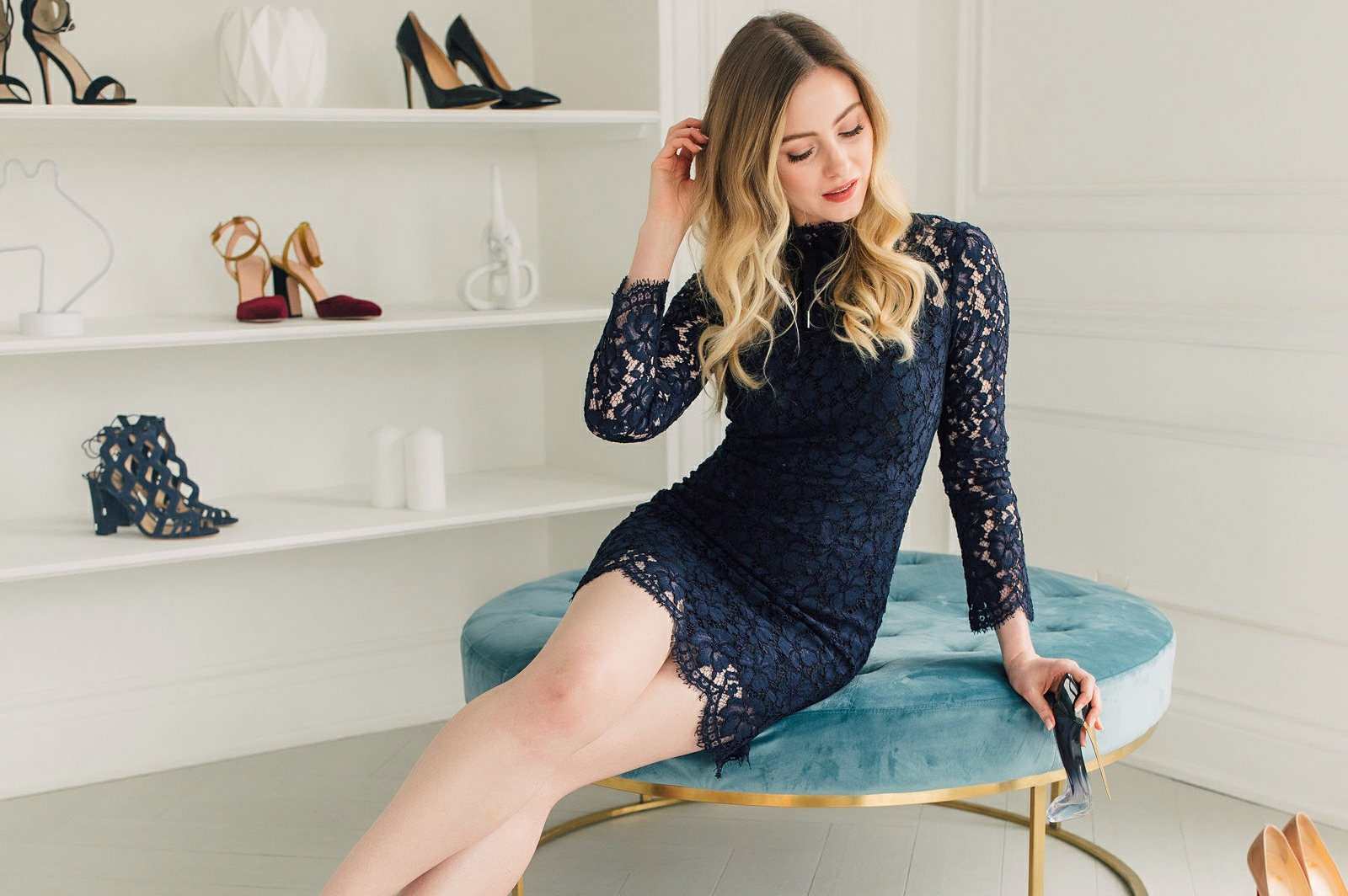 blonde in navy blue lace dress seated on blue velvet ottoman surrounded by shoes at Mint Room Studios