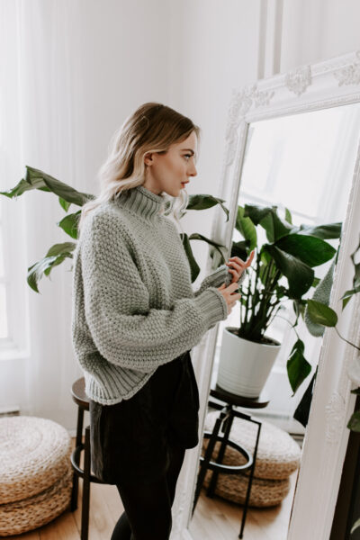 blonde girl wearing mint green wool sweater looking in vintage mirror with white moulding