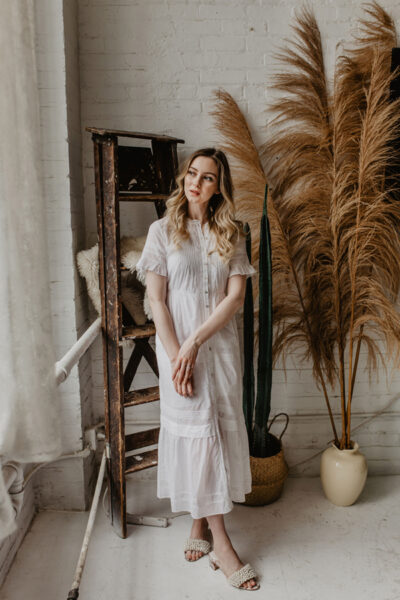 Girl in white bohemian dress next to pampas grass and cactus